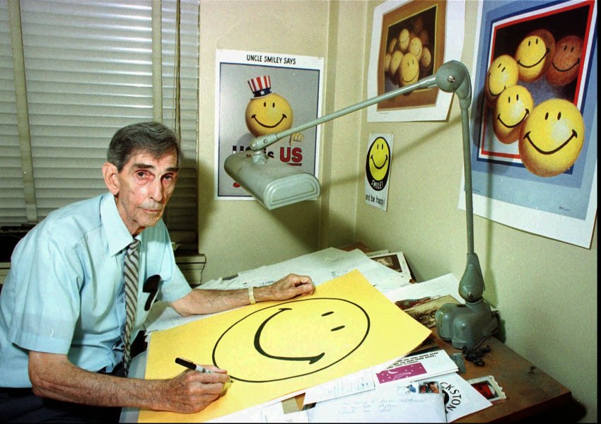 Smiley face creator Harvey Ball, of Worcester, Mass., autographs posters of the internationally recognized symbol for good cheer in his office on Monday, July 6, 1998 in Worcester, Mass. Ball, 76, is upset over French entrepreneur Franklin Loufrani's claim that he created the symbol.(AP Photo/Paul Connors) Smiley-Erfinder Harvey Ball unterschreibt am 6. Juli 1998 in seinem Büro in Wocester, Massachussetts, ein Poster mit dem Strahle-Symbol.